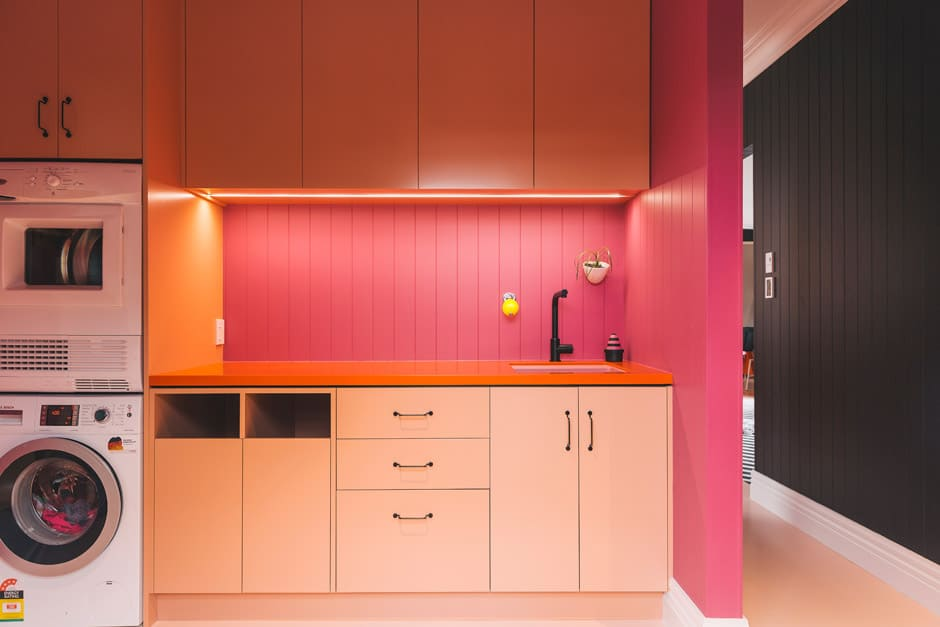 BELOW Accessed from the kitchen, the laundry features the same vibrant colour palette, with the addition of bright pink Dulux Napier. Alex's design for this room included built-in hampers and strip lighting.