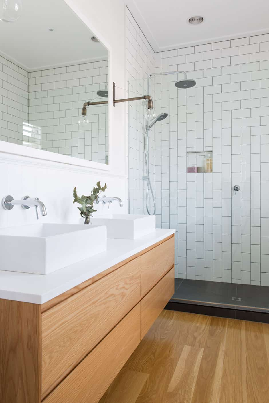 BATHROOMS American oak floorboards feature throughout the house, including in the main bathroom (opposite) and ensuite (below right), where wall lights from Father Rabbit lend an industrial vibe. BEDROOMS A Fog Linen garland from Father Rabbit prettifies the wall above the guest bed (top left), while the special finds in the baby's room include a rug by Jamie Kay (above) and a customised to-scale print of newborn Lucia from The Birth Poster (below left).