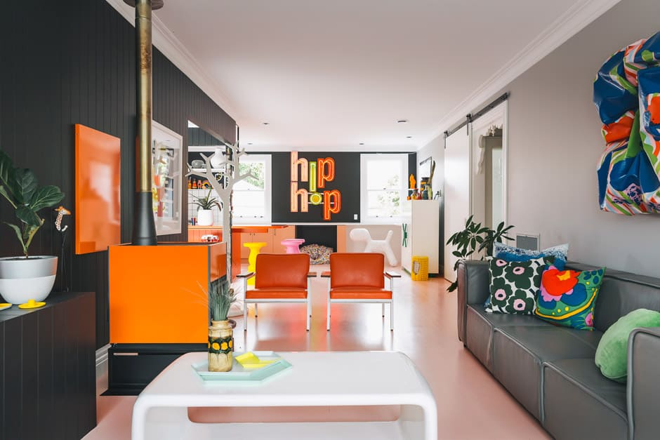 LIVING Orange steel-frame chairs by George Nelson for Herman Miller are a great match for the Pyroclassic fire and sit alongside an embroidered artwork by Rachel Castle. The floor is painted in Dulux Pale Blush. LIVING From the playful collections of curios to the meticulous finishings of the architraves, the renovation has successfully integrated the boldly modern while honouring the villa's heritage. Here, the Hip Hop neon light is from World, and the sculptural 3D painting on the right is by Miranda Parkes.