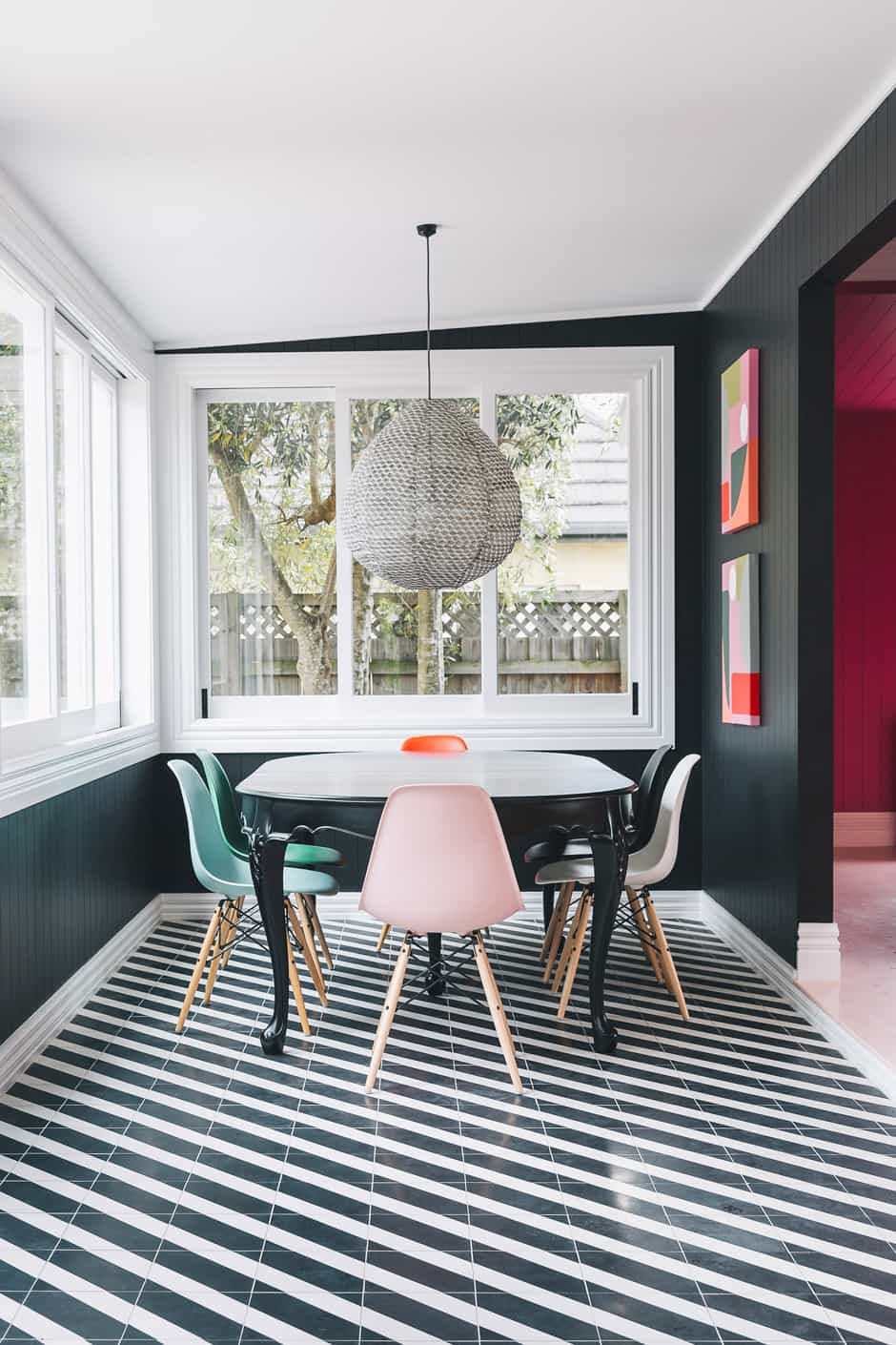 DINING A pendant light by Paris au Mois d'Août from Madder & Rogue, Eames chairs, and a dining table found on Trade Me and painted in Dulux Blackwood Bay (the same shade as the walls) are complemented by Alex's own artworks, The Twins. She and Daisy are pictured opposite.