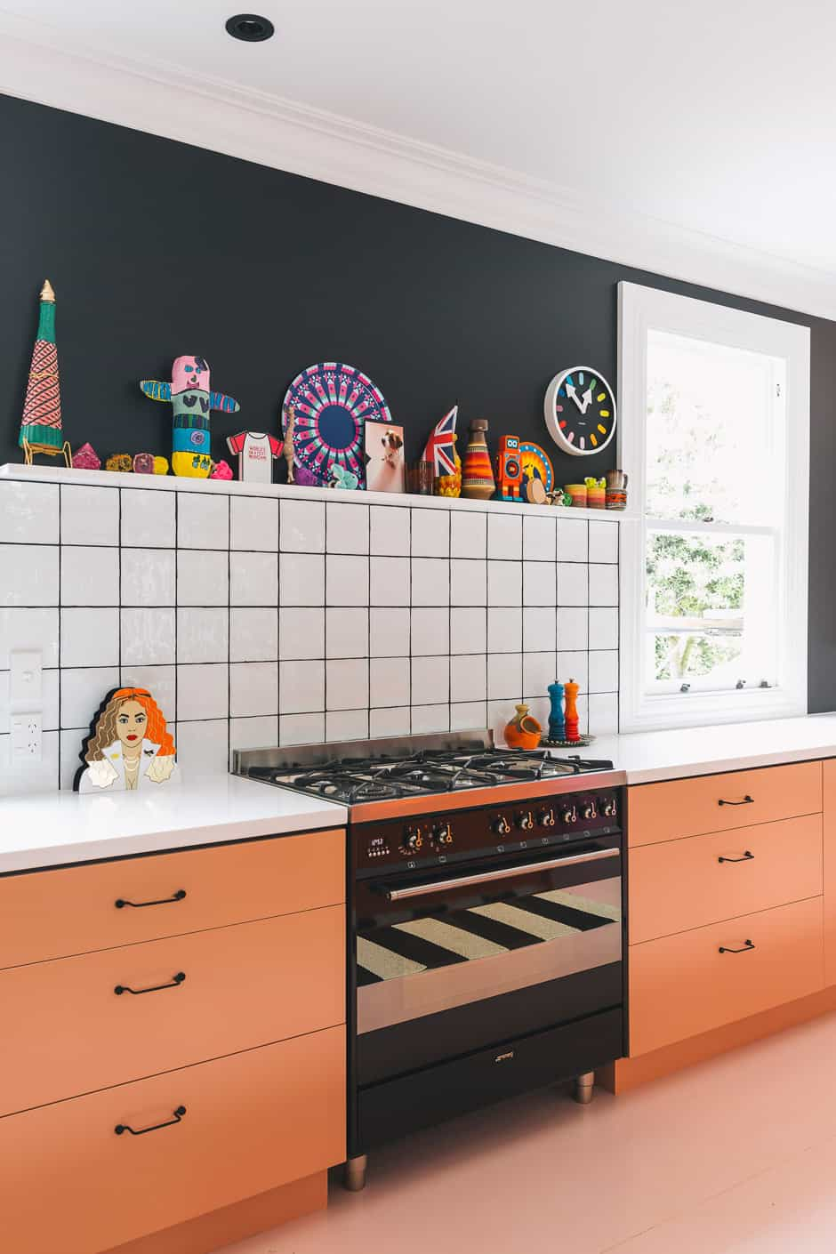 "KITCHEN The cabinetry is enlivened with Dulux Hot Embers and Dulux Broadway. ""Creating a black negative detail added a luxe component that brought a modern element to a stock MDF design,"" adds Alex. BELOW Accessed from the kitchen, the laundry features the same vibrant colour palette, with the addition of bright pink Dulux Napier. Alex's design for this room included built-in hampers and strip lighting."