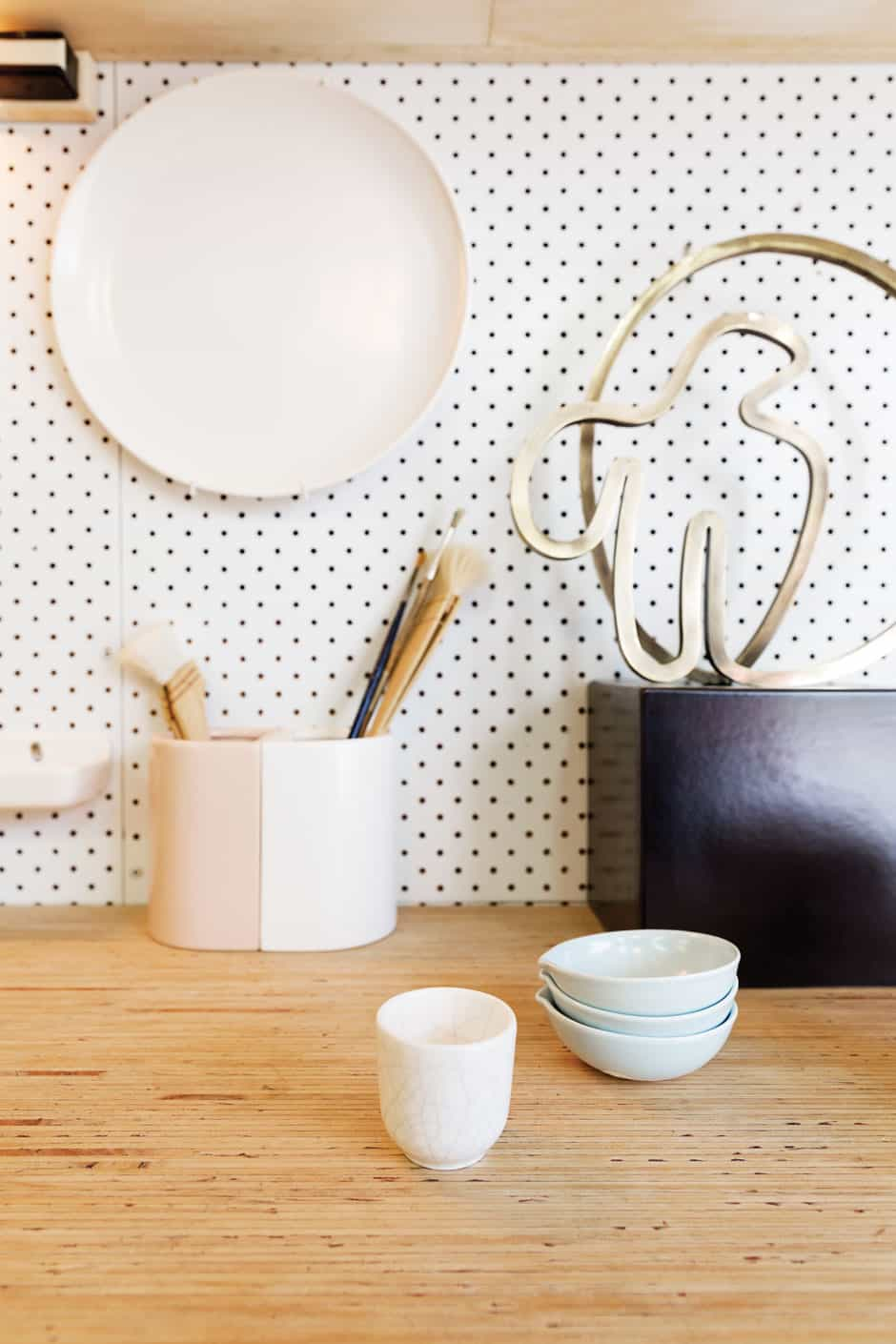 RIGHT Domestic ware from Gidon's ceramics range sits on the workbench alongside an electroplated brass sculpture and pink-and-white bookends designed for a collaboration between Thing Industries and fashion maven Kate Sylvester.