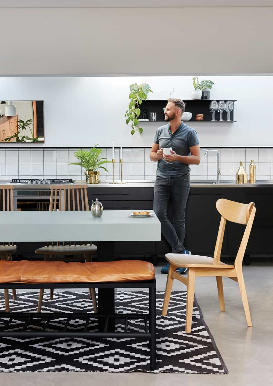 """KITCHEN Even the kitchen units are raised off the floor. Nico (pictured) and Christo incorporated contrasting finishes throughout the house: here the sleek stainless steel benchtop offsets the rough painted walls. A slim steel shelf was placed along the top of the splashback because Nico has always disliked the way tiles """"just end"""". Around the table designed and made by Christo, chairs are mixed and matched to create a casual combination."""