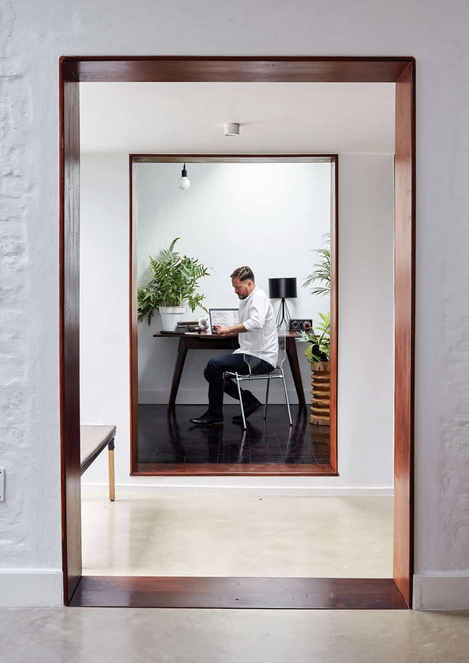 OFFICE Christo is pictured in the entry vestibule connecting the main house to the study, which creates a frame for the vintage desk, the lightness of the composition maintained by a transparent polycarbonate chair. Indoor plants bring an organic element to the clean-lined simplicity of the white, cube-like space, lit from above by skylights. The floor in this area is parquet salvaged from the rest of the house.