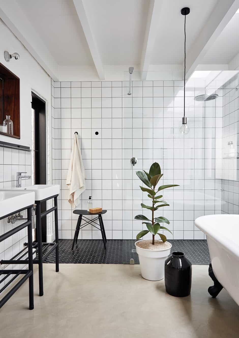 BATHROOM The main en-suite bathroom combines modern fittings with a traditional iron ball-and-claw bath. Christo designed the steel plinths for the basins, and a matching Eames-like stool makes a handy repository for bathing accessories. The narrow door leading to a courtyard outside is one of Nico's favourite features as it creates the sensation of being in an outdoor shower.