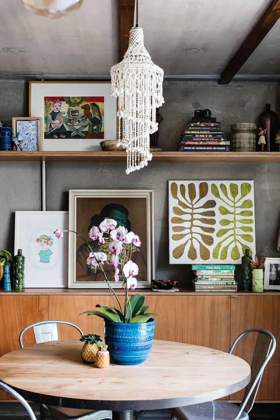 SHELVE IT In the dining area, where the family gathers at the $20 op shop table the couple sanded and painted, Susanna's framed illustrations rub shoulders with an eye-catching collection of vintage paintings and souvenirs, as well as pottery finds from Australia and Paul's native New Zealand. Susanna has repurposed her favourite blue Bitossi vase as a planter for an exotic orchid.