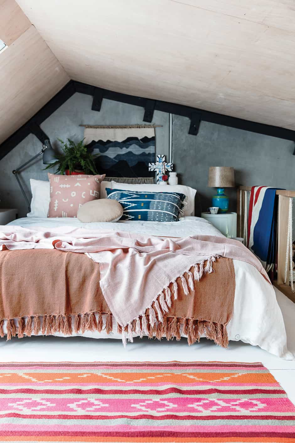 MASTER BEDROOM The couple's attic bedroom is filled to the brim with an eclectic collection of items, including a rug from Argentina, throws by Citta Design and a Componibili storage unit by Anna Castelli Ferrieri for Kartell paired with a thrift store lamp.